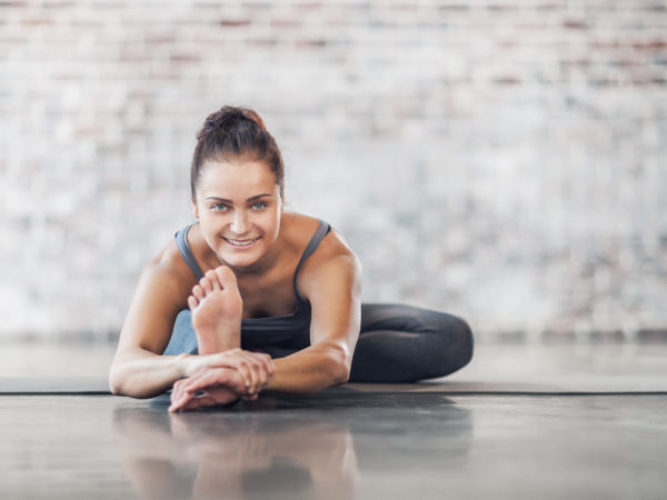 Young Woman Doing Yoga Meditation and Stretching Exercises. Stock photo.