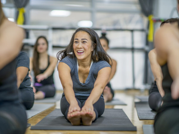 A multi-ethnic group of adult women are indoors at a health center. They are all wearing grey athletic clothing. An Asian woman is in focus, and she is laughing while stretching to touch her toes.