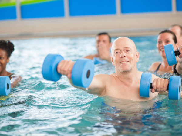 A multi-ethnic group of adults and senior adults are taking a water aerobics class in a public pool together. They are holding floating weights are are moving their arms.