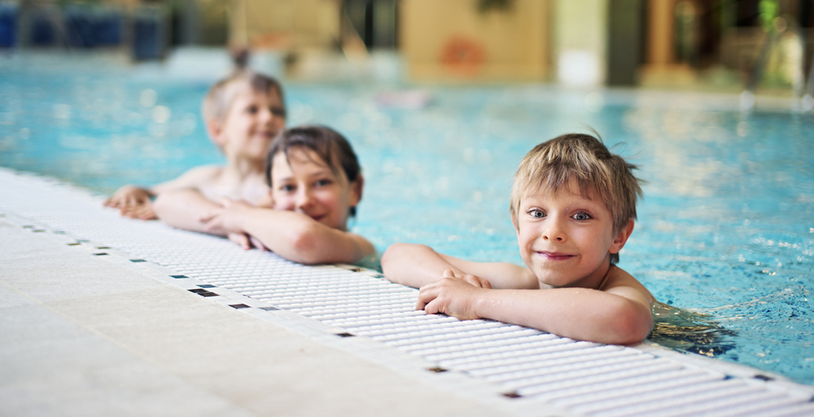 Happy kids having fun in indoors swimming pool. The boys are aged 5 and the girl is aged 9. Everyone is smiling at the camera.