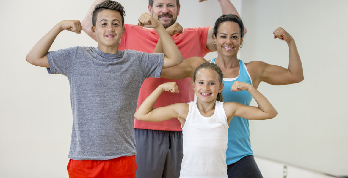 A family of four are working out together at the gym. They are flexing their muscles and are smiling while looking at the camera. a