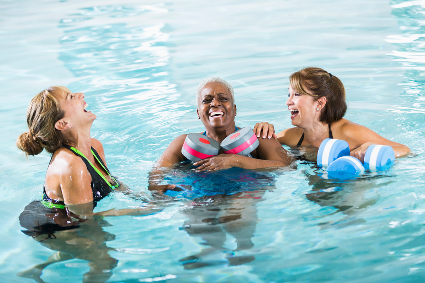 A group of three multi-ethnic women standing in a swimming pool holding dumbbells used for water aerobics.  They are taking a break from their exercise routine, laughing hysterically.